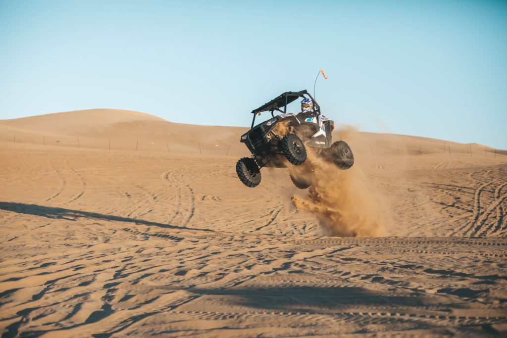 man riding a used UTV on desert during daytime