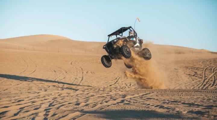 man riding a used UTV on desert during daytime